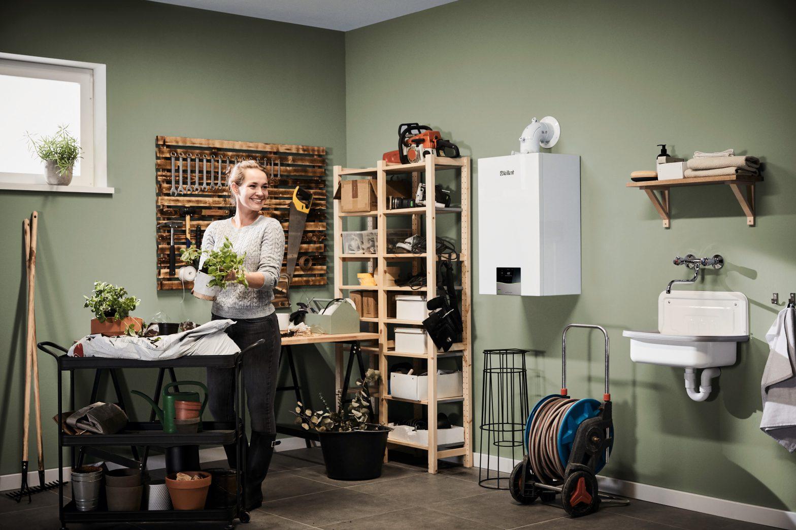 Kobieta przesadza rośliny w kotłowni z gazowym kotłem kondensacyjnym